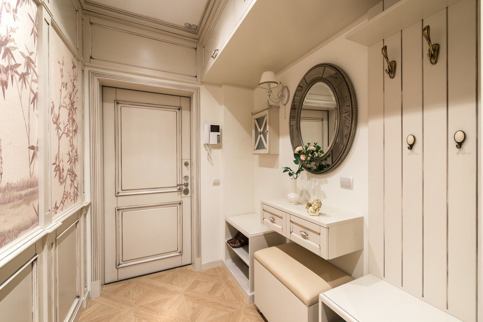 The white foyer offers wall mounted hooks and a stylish round mirror that hung above the floating cabinet with a cushioned seat underneath. It has a simple entry door and light hardwood flooring arranged in a diamond pattern.