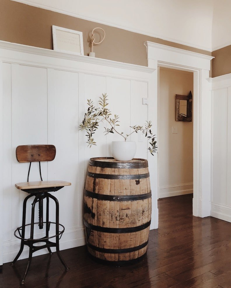 Shabby chic foyer with a zen vibe through the gorgeous potted plant that sits on the rustic barrel. It is complemented by a high metal chair over the dark hardwood flooring.