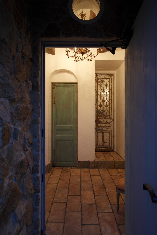 A wood plank entry door against the stone walls open to this small foyer with brick flooring and white inset walls fitted with distressed doors.