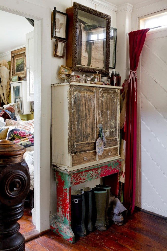 An eclectic gallery hangs above the reclaimed cabinet that sits on a high distressed base making it a perfect spot for boots. There's a white entry door on the side that's accented by a lovely red drapery.