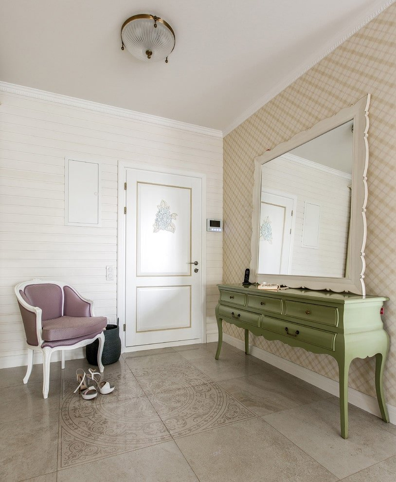A large white mirror complements the green console table situated against the beige plaid wall. It is accompanied by a classy cushioned chair and a white door accented by gold trims.