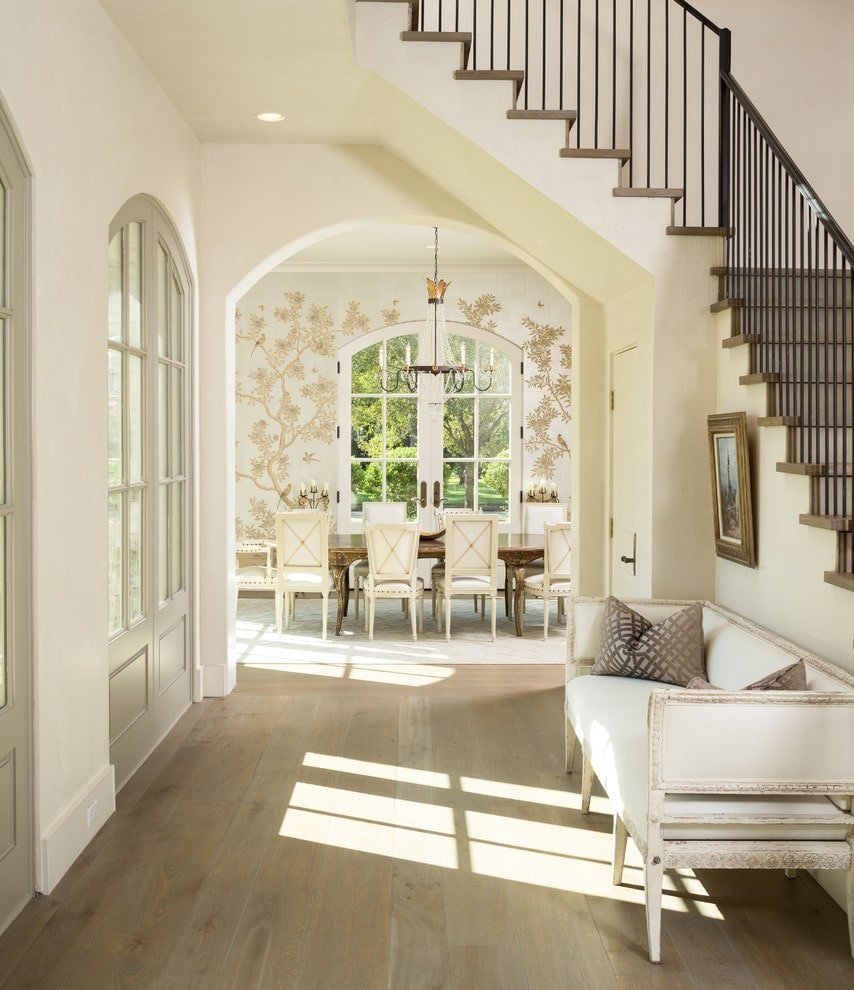 Natural light streams in through the French door in this foyer with a wooden framed artwork and a white cushioned seat against the staircase. It has light hardwood flooring and an open archway leading directly to the dining area.