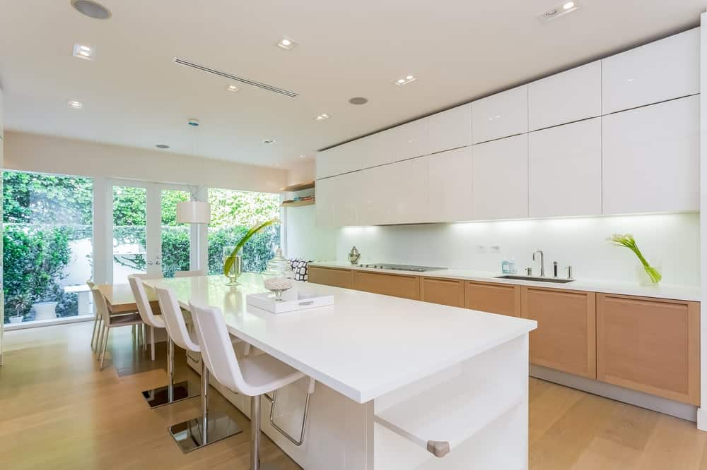 A single wall kitchen with a large white island with space for a breakfast bar paired with white modern bar stools.