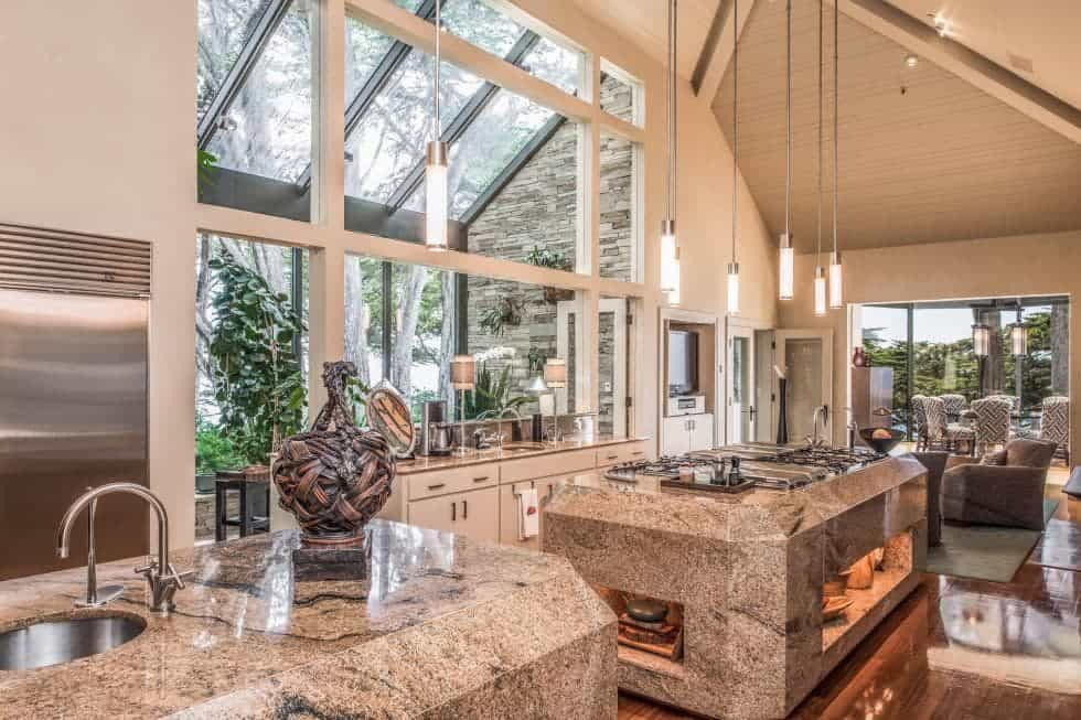 This is the large main kitchen with luxurious marble kitchen islands topped with a tall arched ceiling that hangs pendant lights over the kitchen islands.