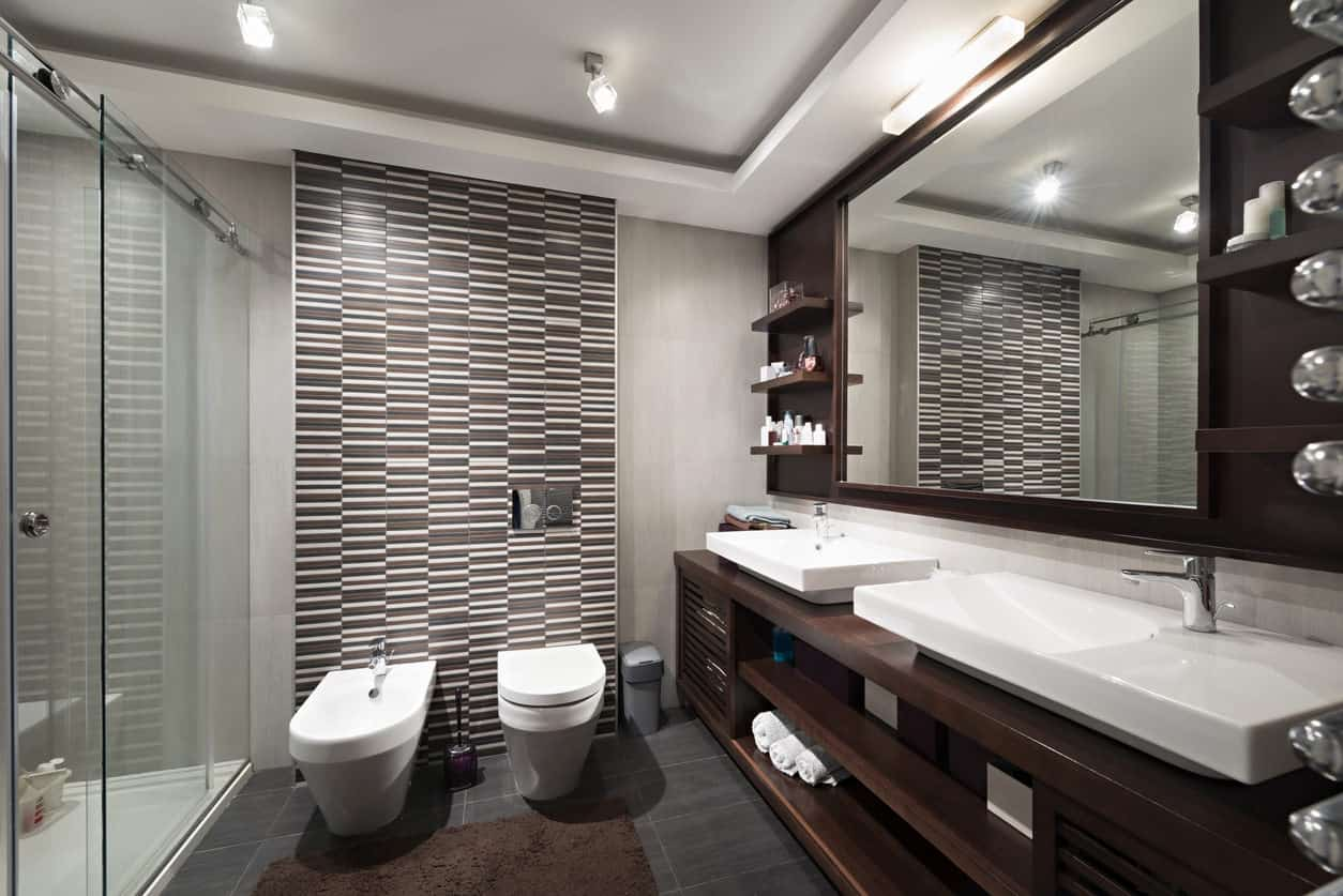 A sleek modern primary bathroom with a stylish wall and a large sink counter with built-in shelving and drawers. It also features a couple of massive vessel sinks and a walk-in shower room.