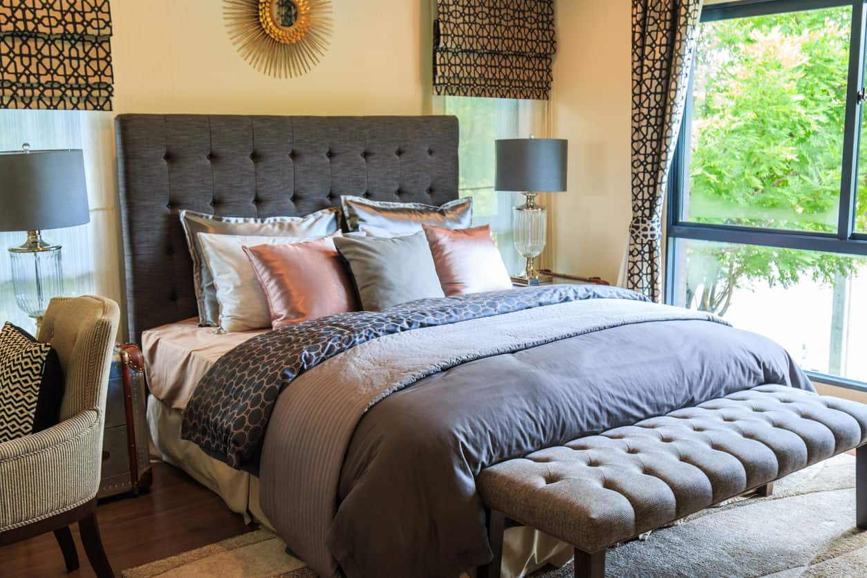 A closer look at this small primary bedroom with dark hardwood flooring and glazed windows dressed in matching drapes and roman shades. It includes gray tufted bench and bed accented with a gold sunburst mirror.