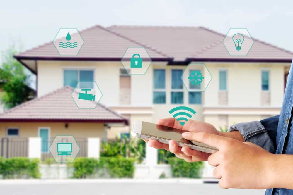 Hands tapping a smartphone connected to a smart home system.