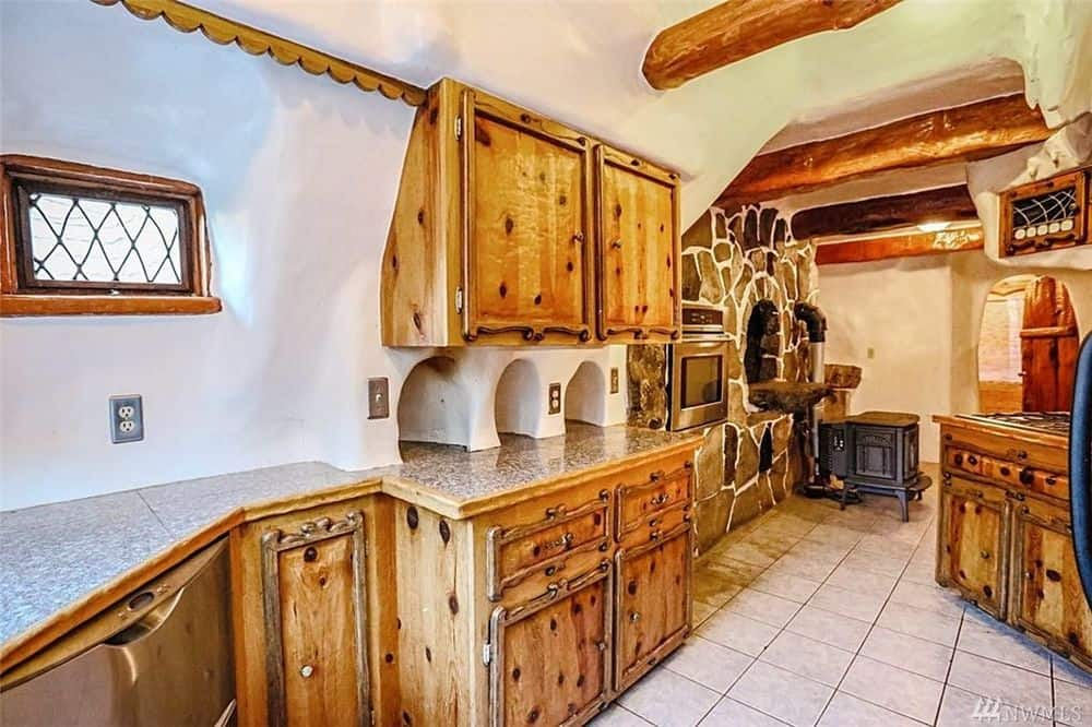 The kitchen has rustic wooden cabinetry complete with scorch marks that give them character and an authenticity. This pairs well with the exposed log beams of the ceiling as well as the stone wall that houses a wood-burning oven.