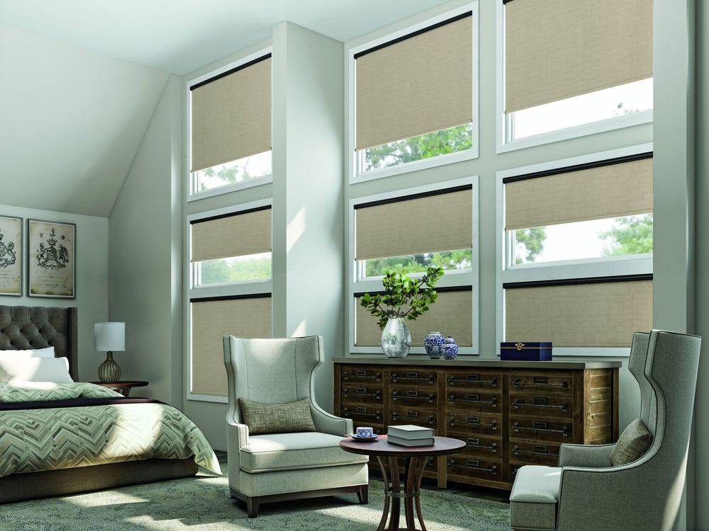 Solar Shades in a luxury bedroom with a seating area.