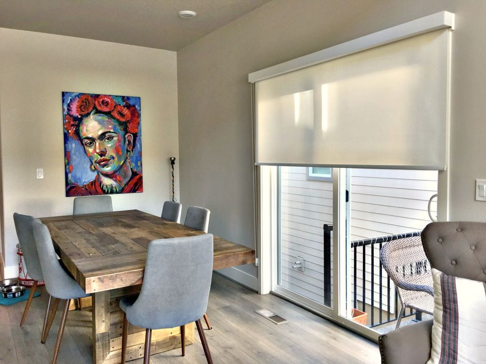 Solar Shades Used on a Sliding Door in a Dining Room Featuring a Frida Kahlo Painting and Reclaimed Wood Dining Table
