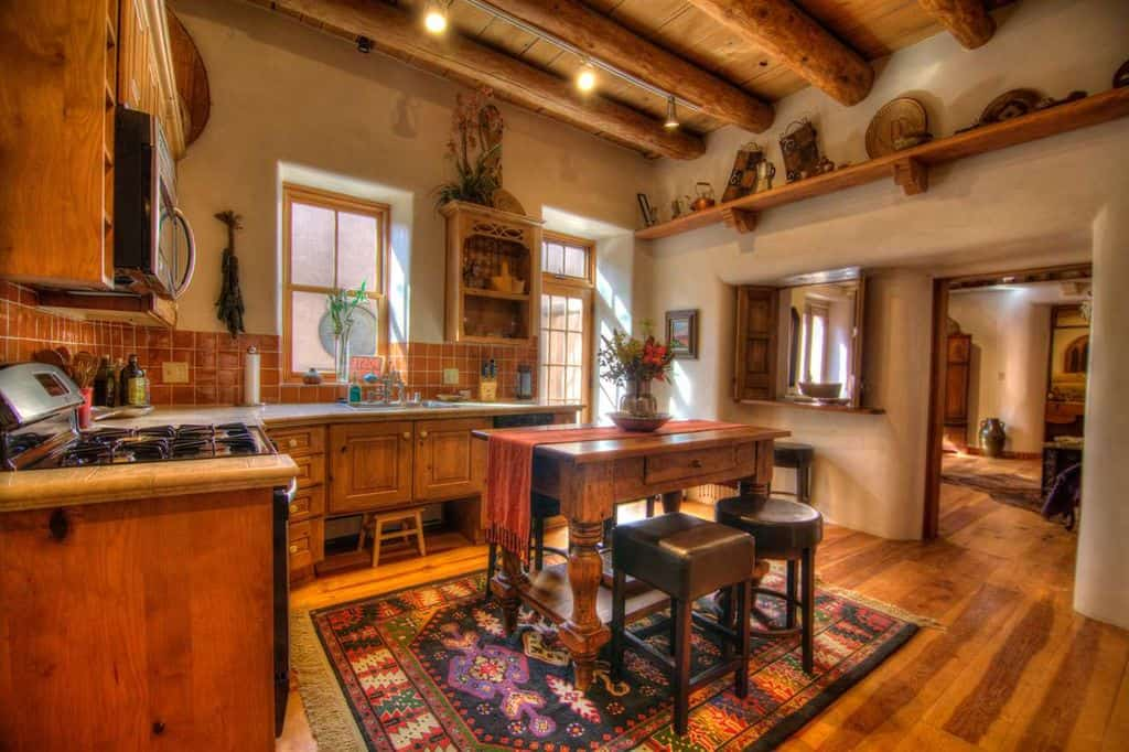 This Southwestern-style kitchen has a wooden ceiling with exposed wooden log beams that give it a rustic quality. This goes great with the L-shaped cabinetry on the walls that have wooden cabinets and drawers and matching brown tiles to its backsplash. A dash of color comes from the colorful patterned area rug in the middle of the hardwood flooring.