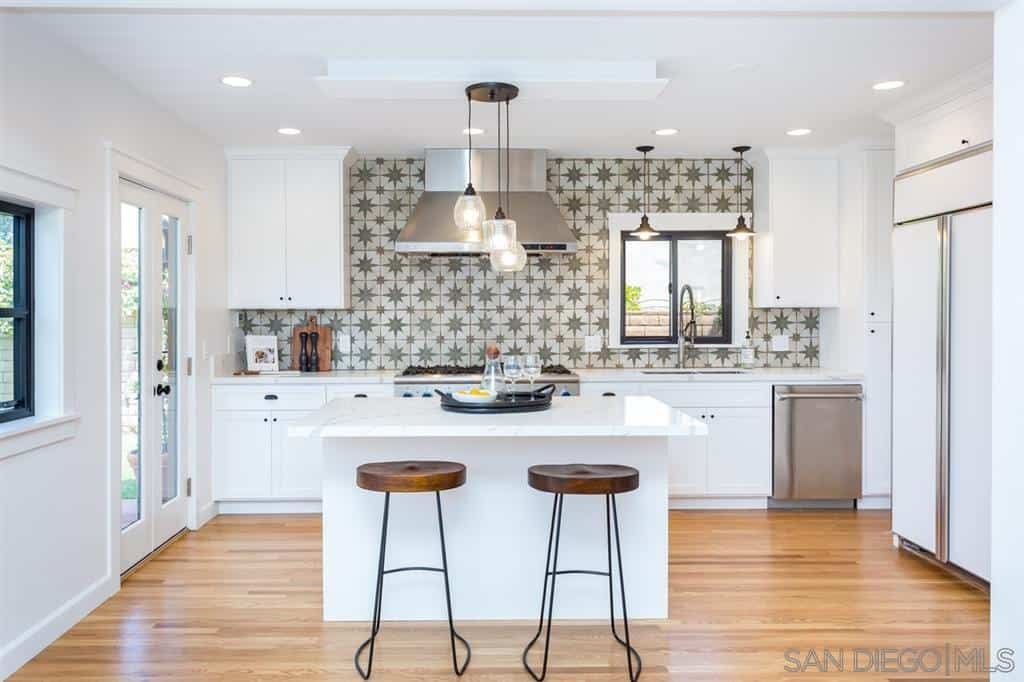 The beautiful patterned wall of this bright and airy Spanish kitchen is a nice contrast to the white shaker cabinets and drawers of the wooden structure housing the stainless steel appliances. This is across from the small white kitchen island in the middle of the hardwood flooring.