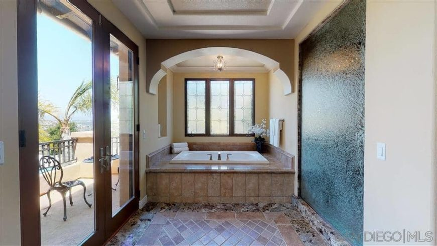 Spanish-style master bathroom with tiles flooring and a tray ceiling. It has a deep soaking tub and a walk-in shower room. There's a doorway leading to a private balcony as well.