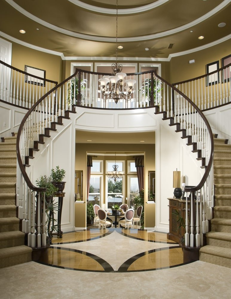 This beautiful entry boasts a luxurious staircase with carpeted steps. The area features gorgeous decorated flooring and a stunning two-storey ceiling.