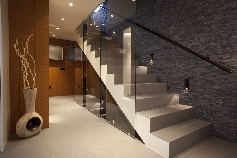 A modern apartment featuring brown walls and tiles flooring, along with a modern straight staircase.