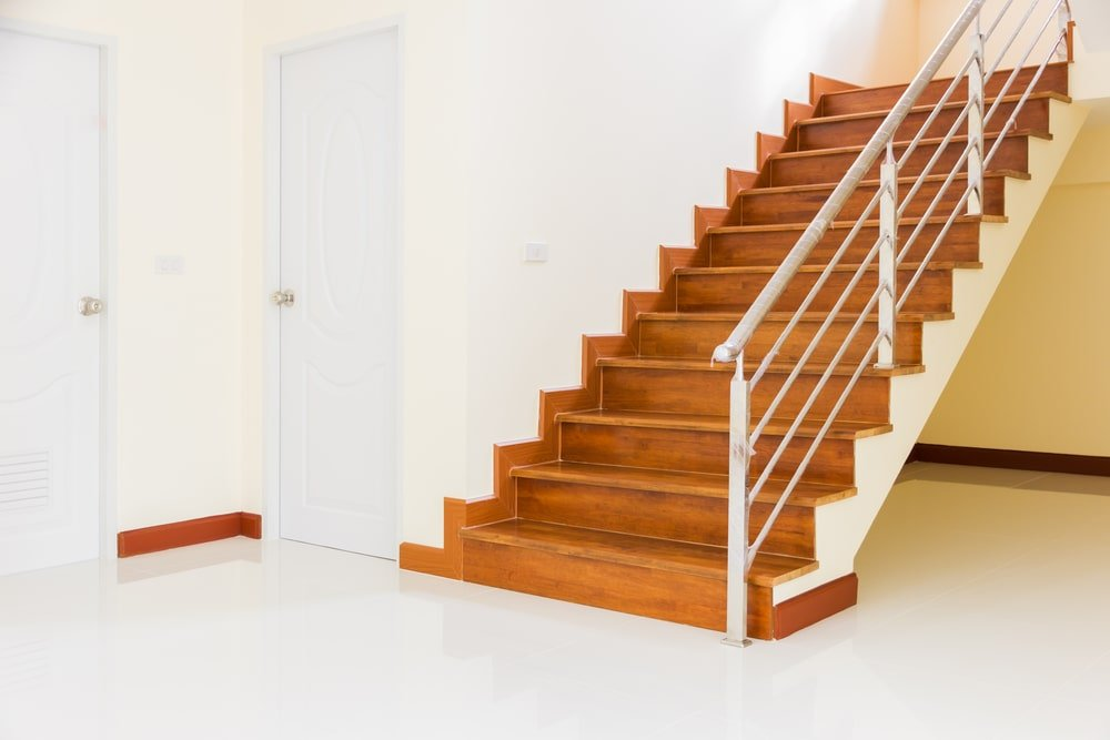 A bright entryway with a wood tone straight staircase with a stainless steel handrail.