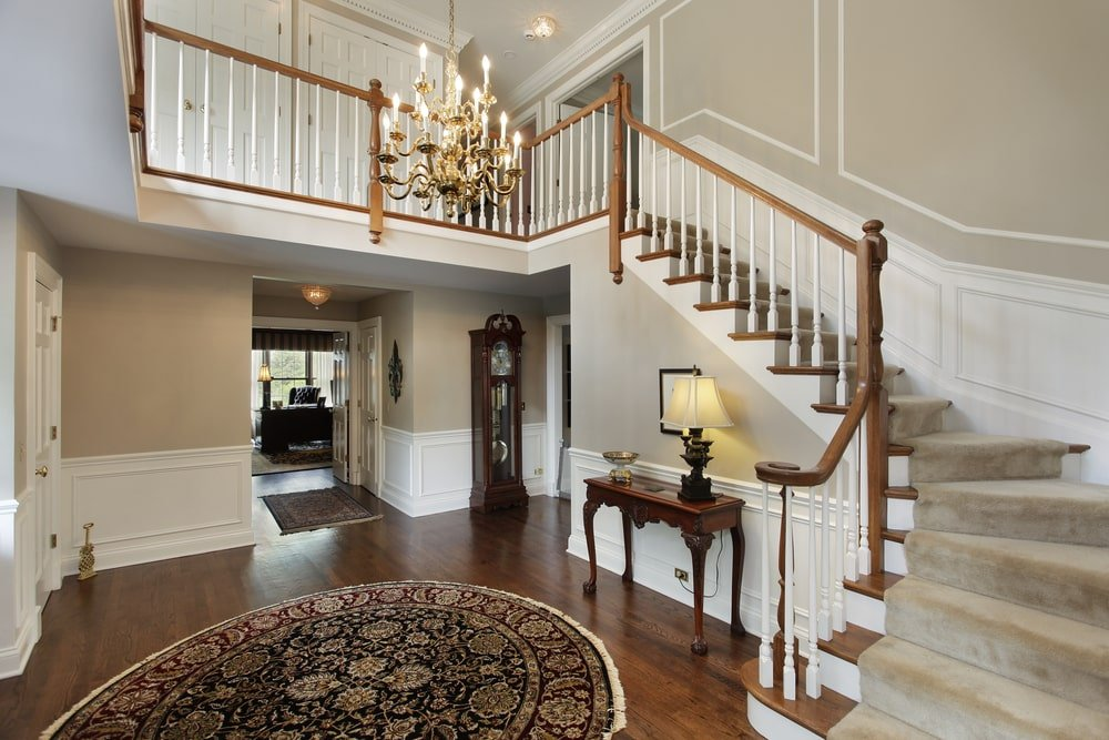 A luxurious foyer with hardwood floors topped by an area rug. The staircase features carpet steps, along with a chandelier lighting hanging from the two-storey ceiling.