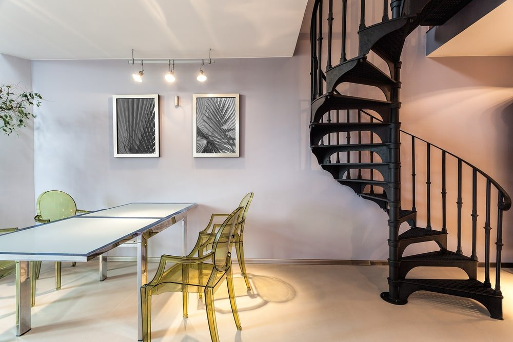 Metal spiral staircase covered in black paint, situated near the home's plastic table and chairs set.