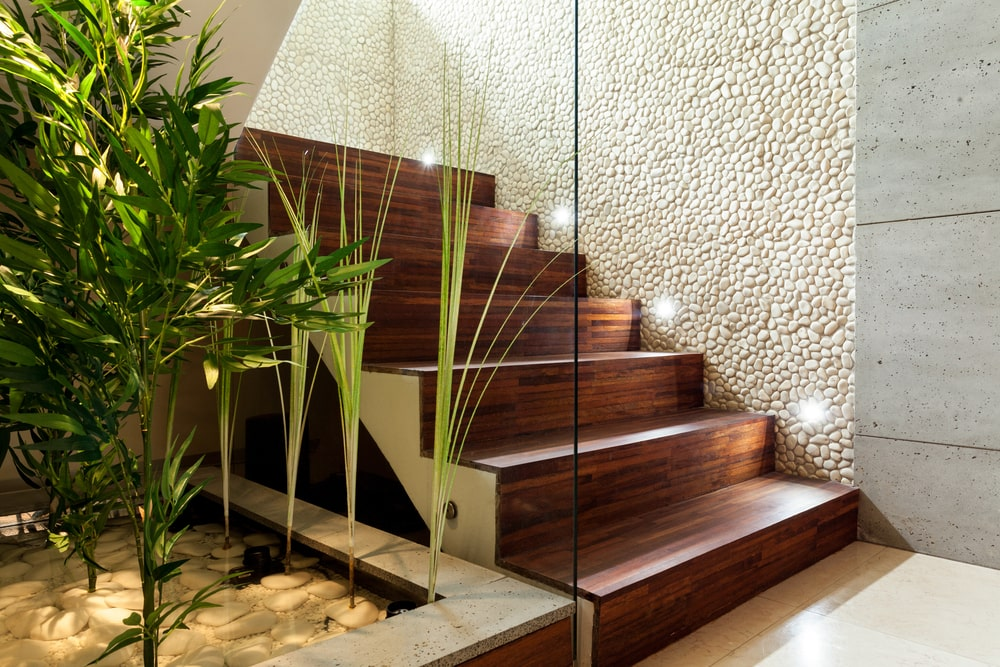 A gorgeously illuminated wooden staircase with glass railings and hardwood steps.