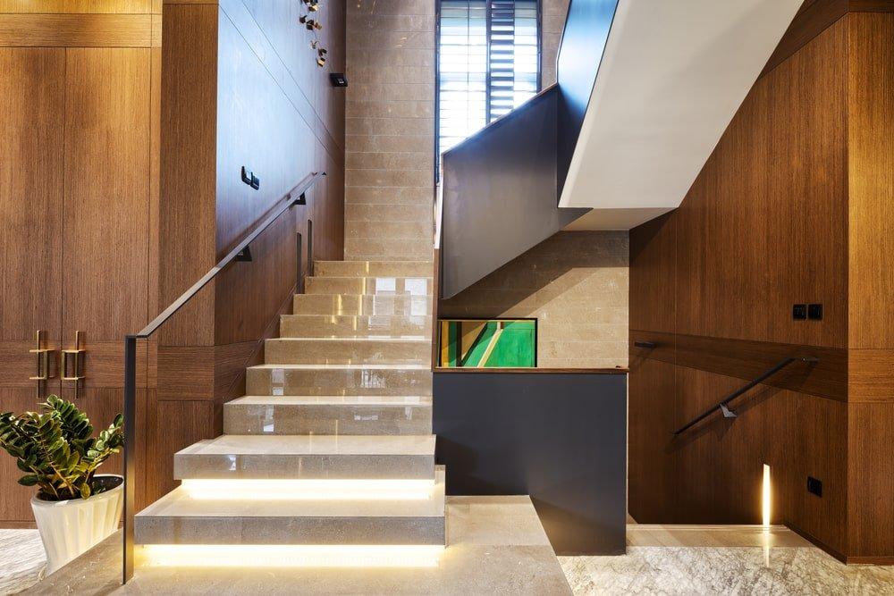 A focused look at this modern staircase with illuminated steps and has glass railings.