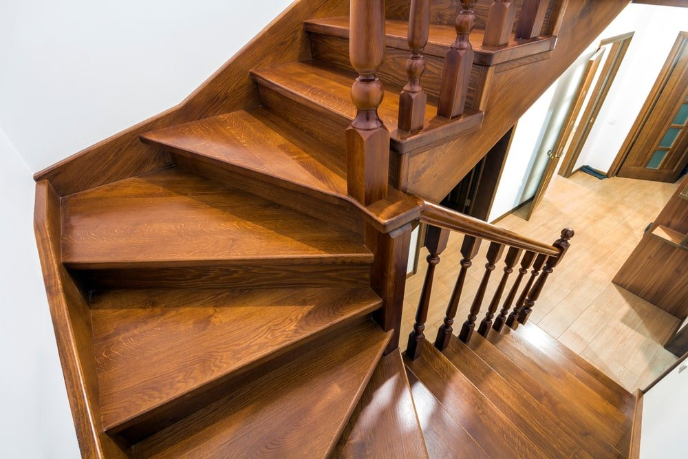 A close-up detail of this brown wooden stairs surrounded by the home's white walls.
