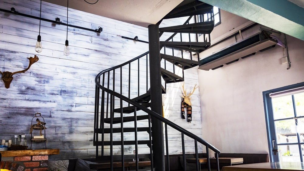A focused look at this spiral staircase made of dark hardwood. The home boasts stylish walls and a tall ceiling.