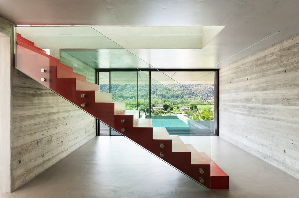 This villa boasts a modern staircase finished in red, featuring glass railings.