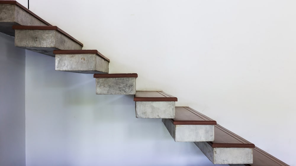 A closer look at this modern home's floating staircase on the white mortar wall.