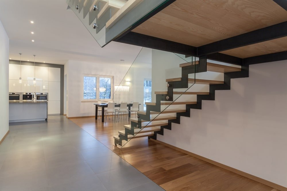 An interior of a modern house boasting a very stylish staircase with glass railings.