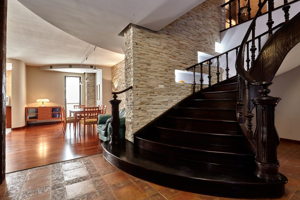 A focused look at this home's elegant dark wood curved staircase with classy wrought iron railings.