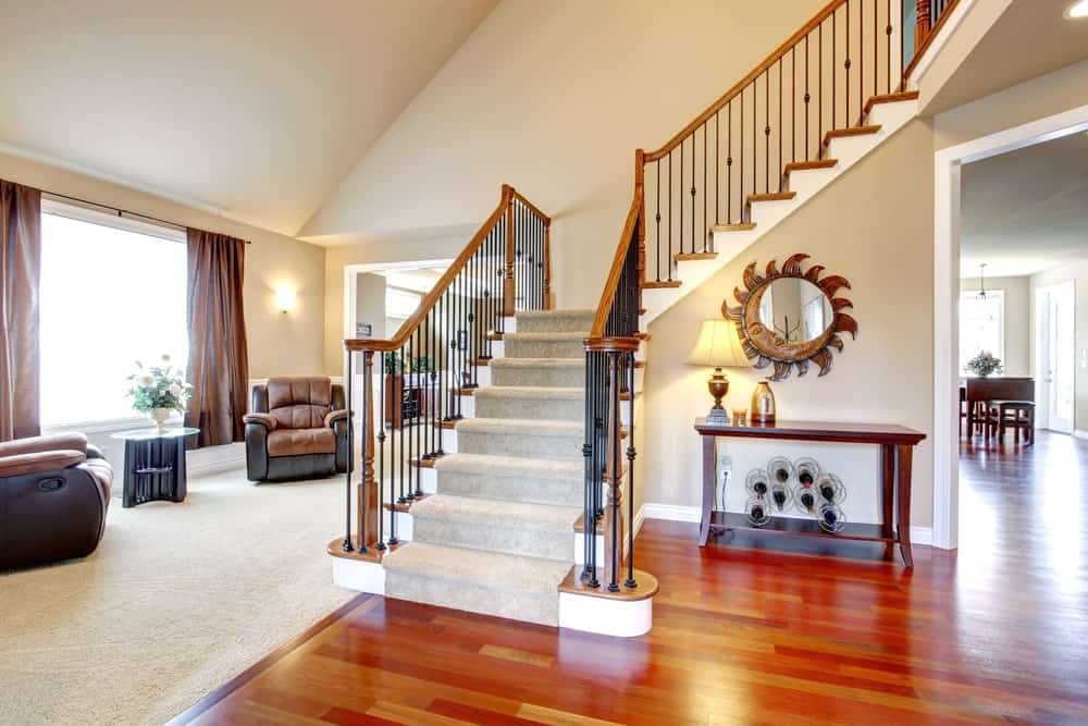 A spacious foyer with carpeted steps and iron railings. The home boasts hardwood and carpeted floors, along with a tall shed ceiling.