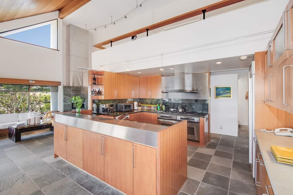 Spacious kitchen with a black marble backsplash. The area features gray tiles flooring and a custom ceiling.