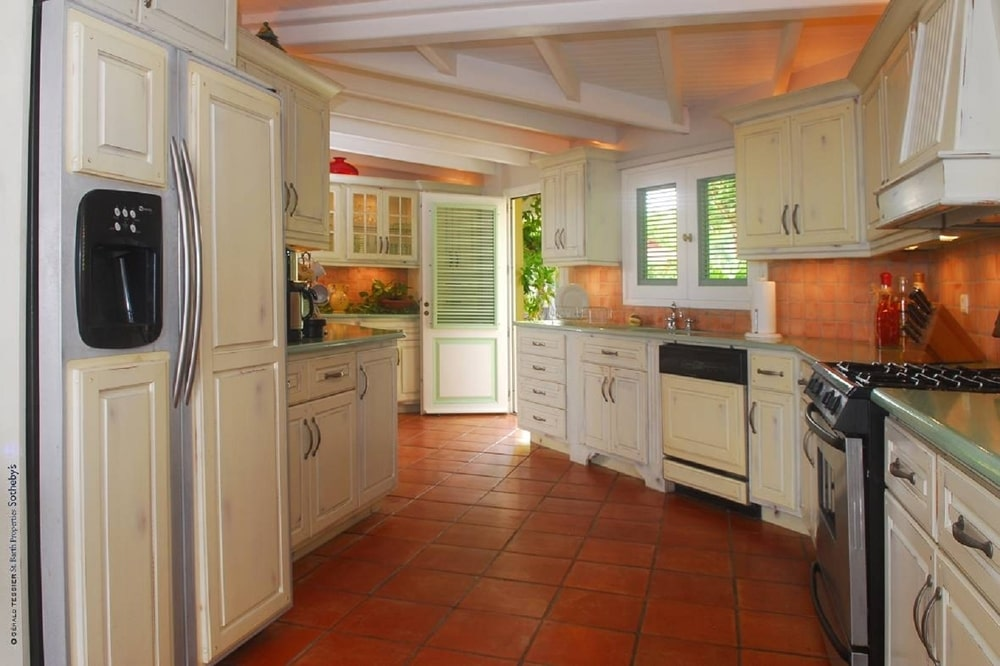 The kitchen has terracotta flooring tiles that complement the beige cabinetry that line the walls paired with terracotta backsplash tiles.