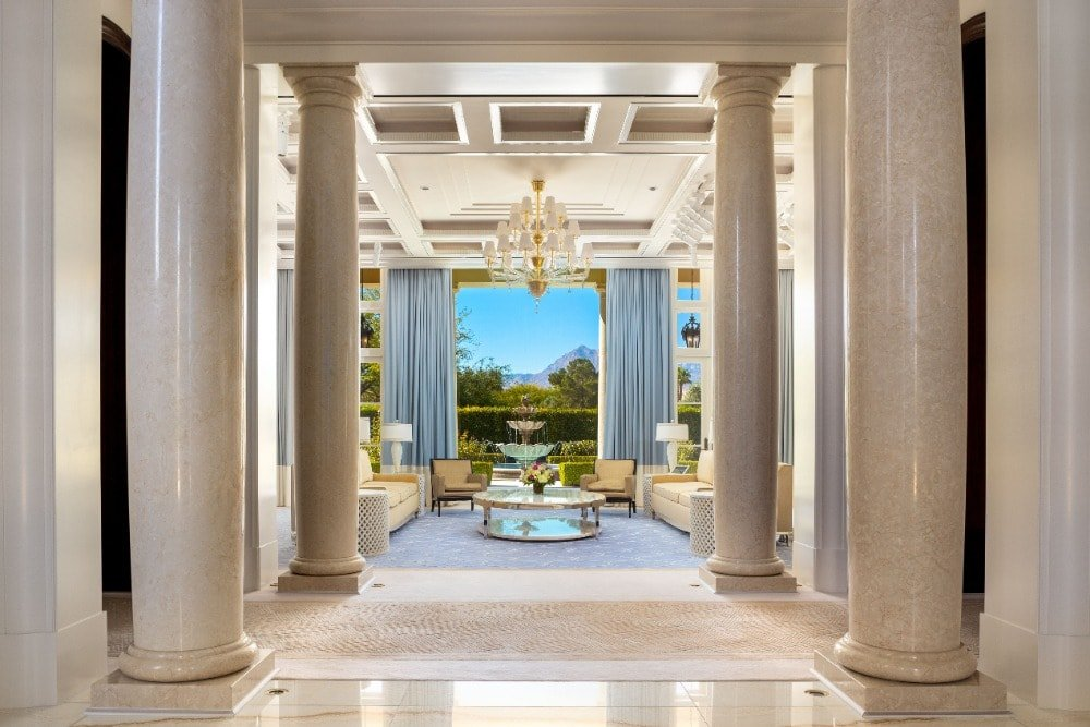 Upon entry of the house, you are welcomed by this beige marble foyer with large beige columns lining the sides of the entryway to the living room.