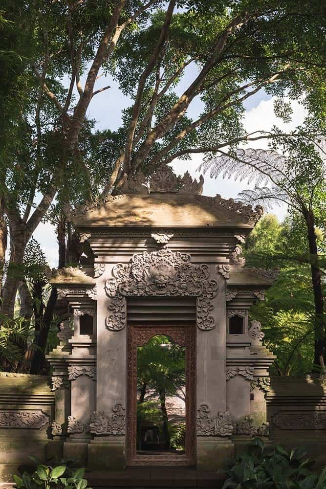 This is a full view of the house's large concrete archway and outer gate with intricate carvings and images on it that gives it a distinct Asian look surrounded by tall trees and shrubs.