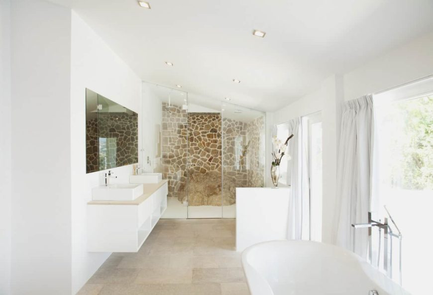 A bright master bathroom with white walls and a white shed ceiling. It boasts a floating vanity with two vessel sinks, a freestanding tub and a stylish walk-in shower.