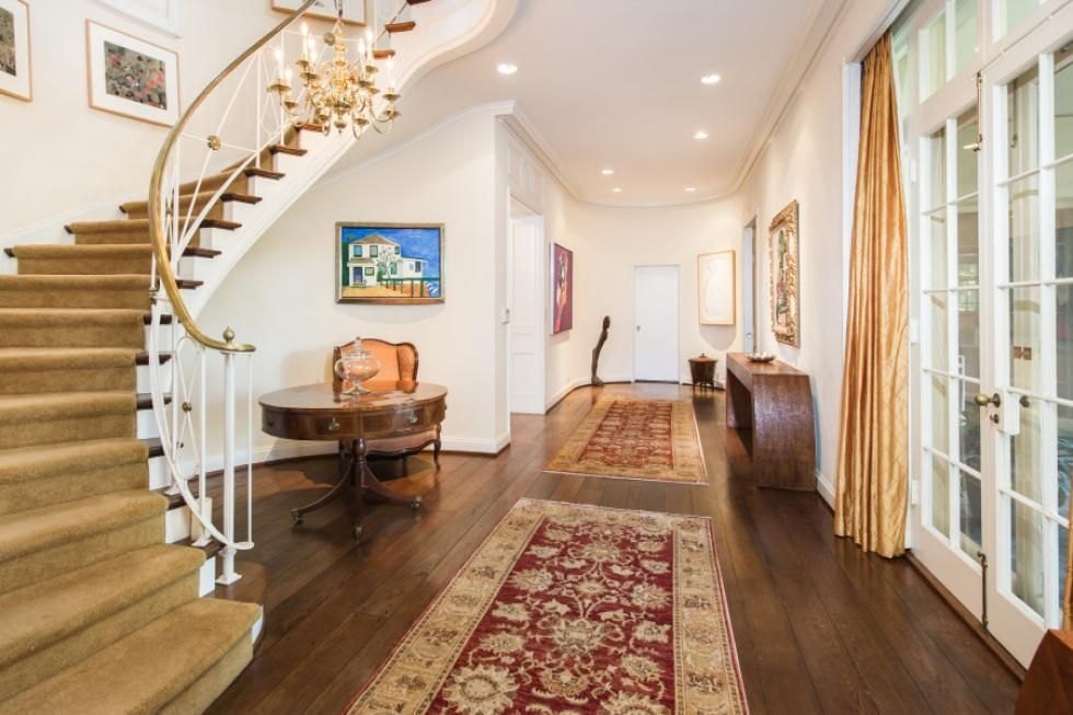 This house's entry features hardwood flooring with a curved staircase on the side of the hall.