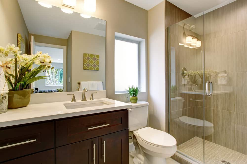 Small primary bathroom featuring a single sink counter lighted by wall lighting along with a walk-in shower room with stylish tiles walls.