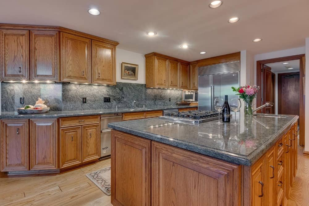 This kitchen boasts black marble kitchen countertop and backsplash. There's also a large center island.