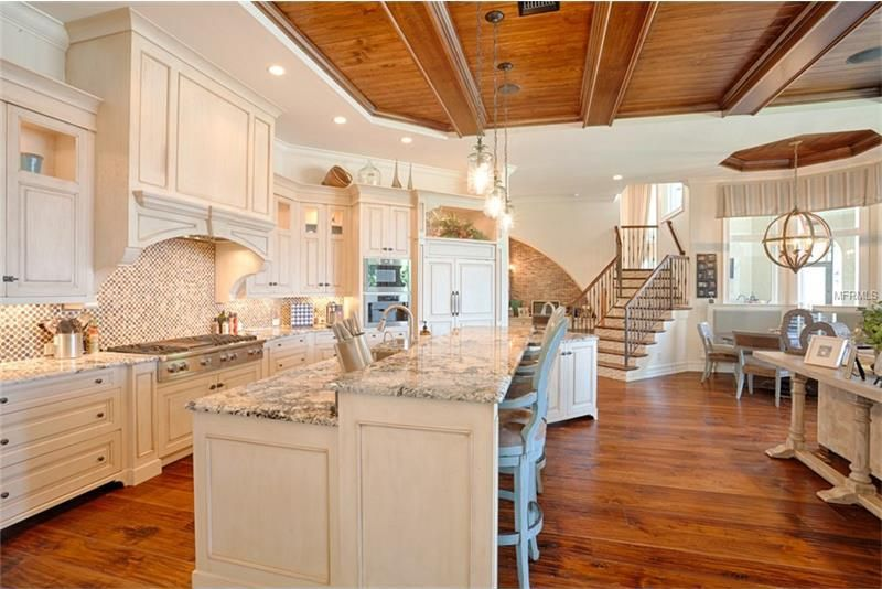This is a closer look at the kitchen with a beige kitchen island that stands out against the hardwood flooring that matches the wooden ceiling with exposed beams.