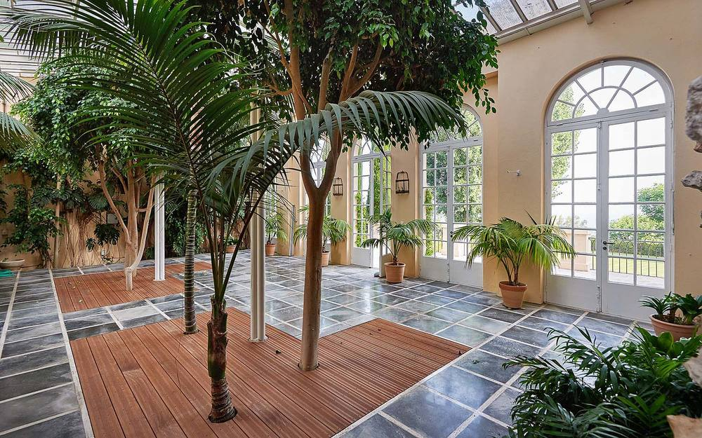 Upon entry, you are welcomed by this bright and airy foyer adorned with potted plants and medium-sized trees that are illuminated by the glass doors and transom windows.