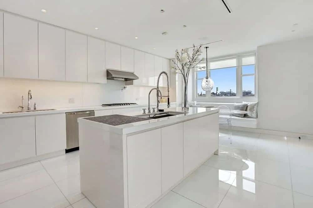 This is the bright white modern kitchen with a large kitchen island that matches the tone of the white-tiled floor and white cabinetry.