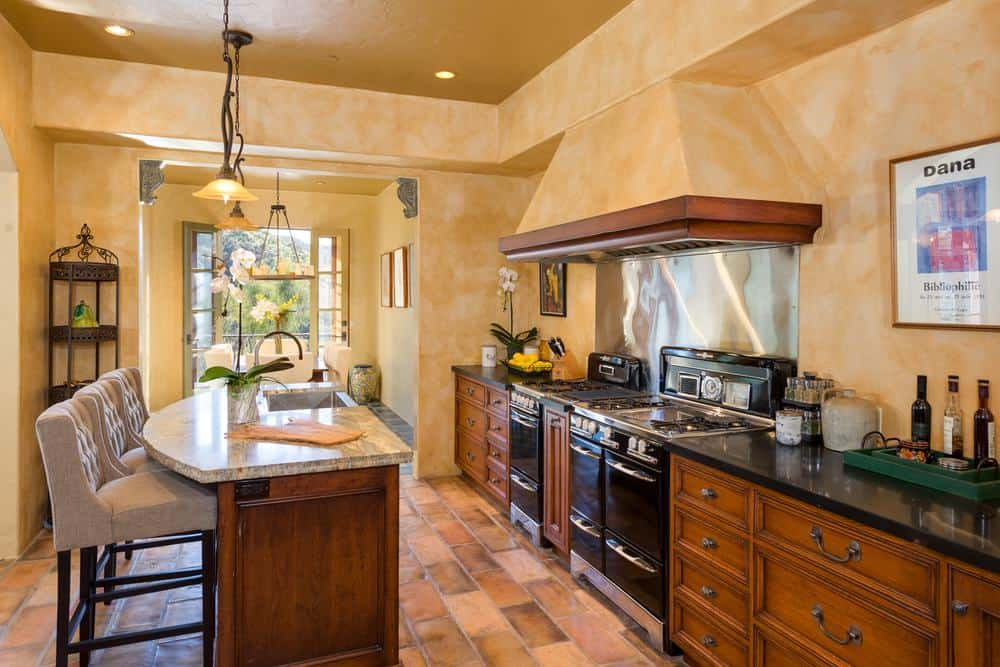 The charming kitchen has a large wooden kitchen island with beige countertop to match the walls and ceiling. These are then contrasted by the black countertop of the cabinetry housing the cooking area.