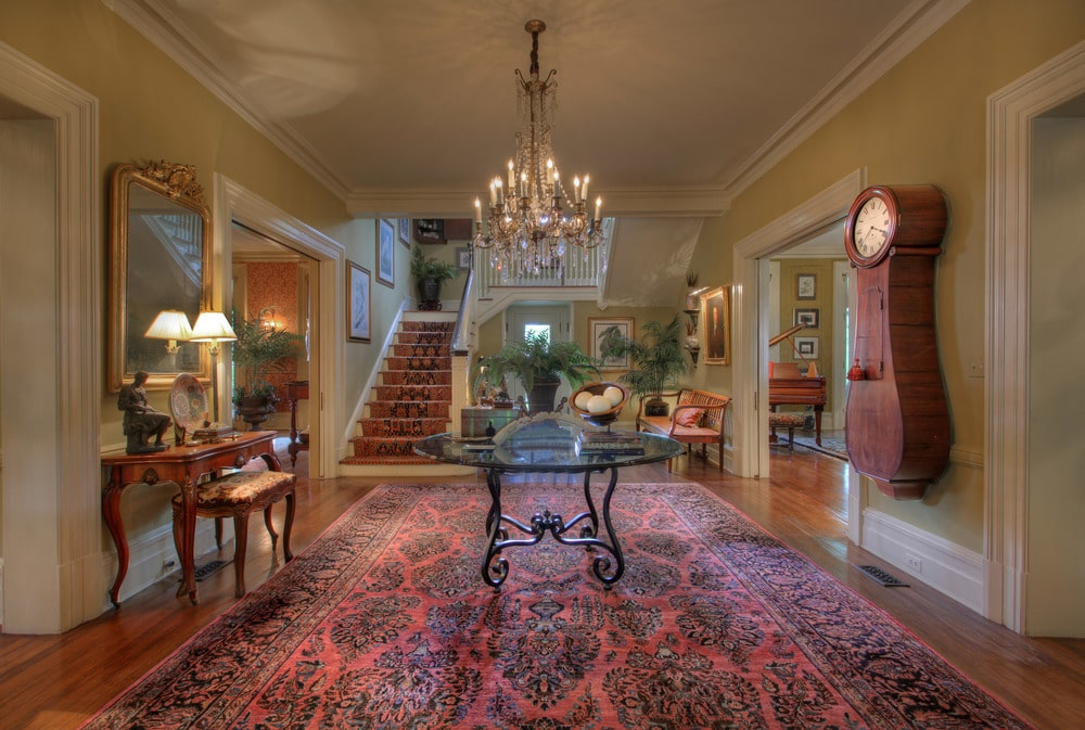 Upon entry of the house, you are welcomed by this foyer with a round glass-top table in the middle under a chandelier.