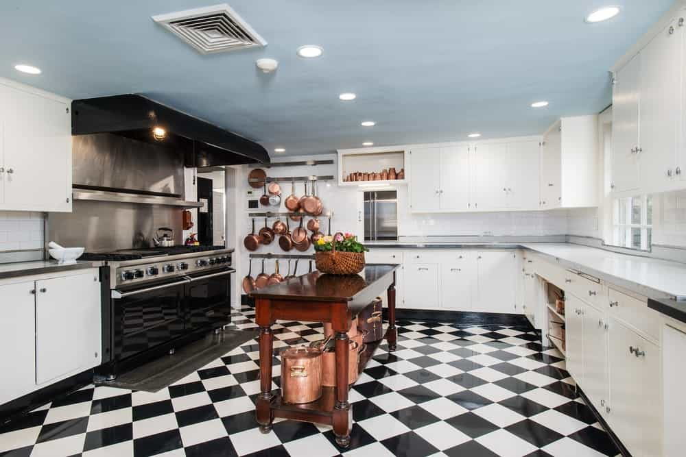 This is a close look at the kitchen that has a wooden kitchen island in the middle of a checkered black and white floor across the large black stove-top oven.