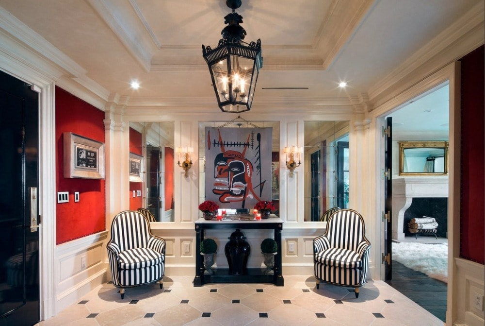 This is the foyer that has a black console table in the middle of two armchairs under a cove ceiling that hangs a black lantern pendant light over the patterned floor.
