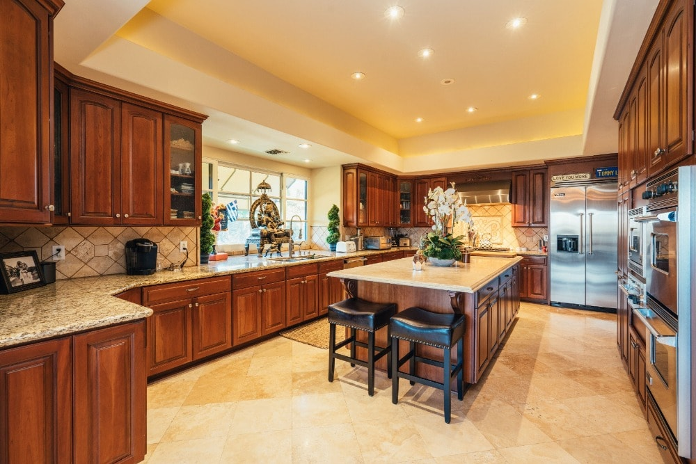The dark wooden kitchen matches perfectly with the surrounding cabinetry that houses the stainless steel modern appliances. These are then complemented by the beige tray ceiling and the flooring tiles.