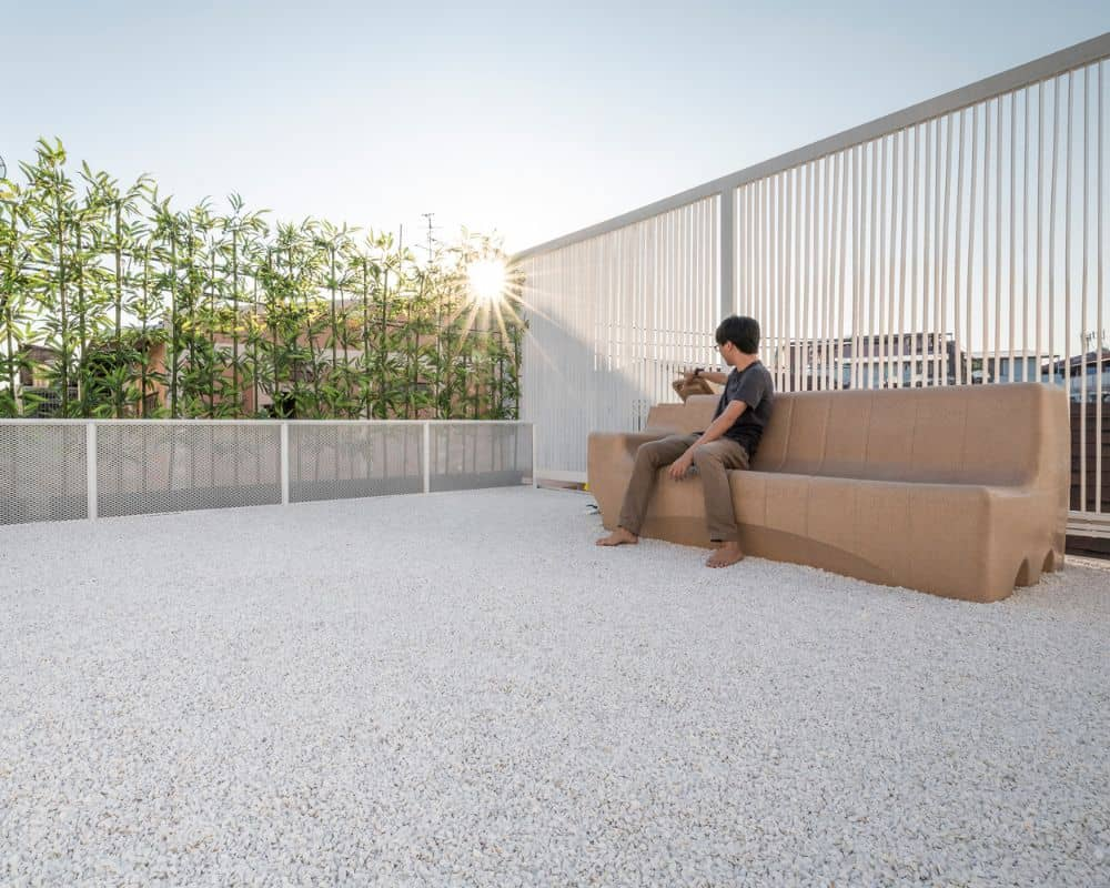 This is a close looka t the rooftop level of the house with a simple landscaping of pebbled flooring, metal grills on one side for safety and a row of bamboo plants on the far edge.