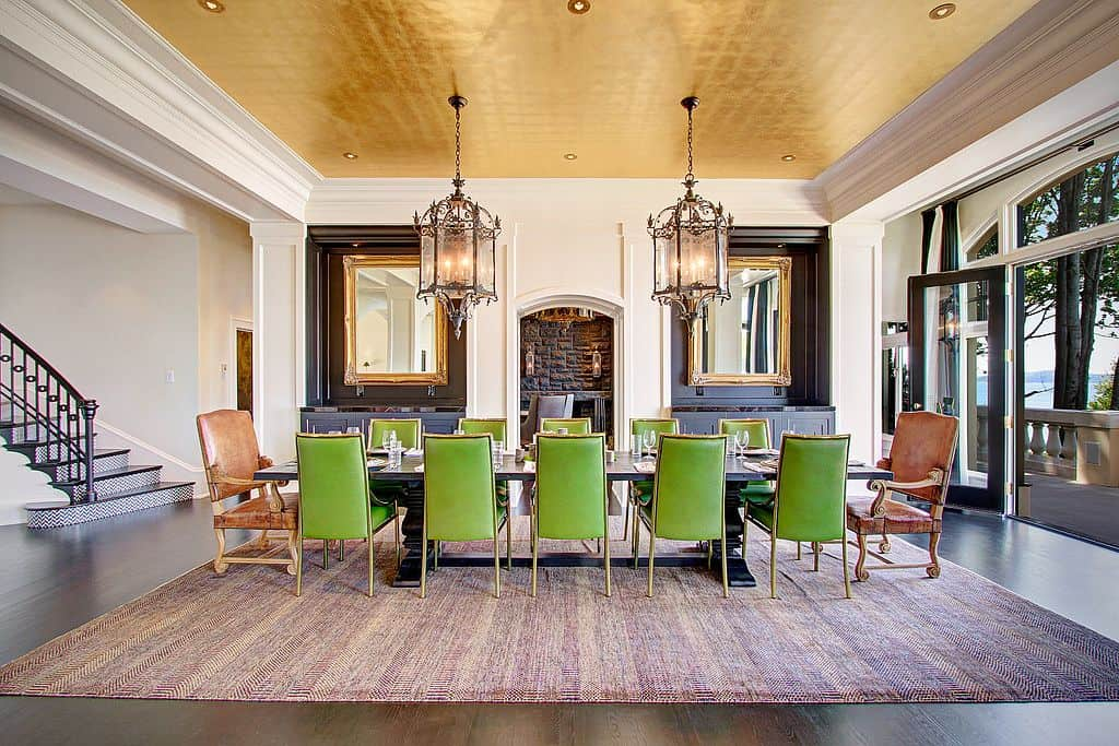 Gorgeous glass chandeliers and brass framed mirrors add a perfect symmetry in this traditional dining room with gold tray ceiling and dark hardwood flooring topped by a large area rug. It offers a long dining table paired with green and brown chairs.