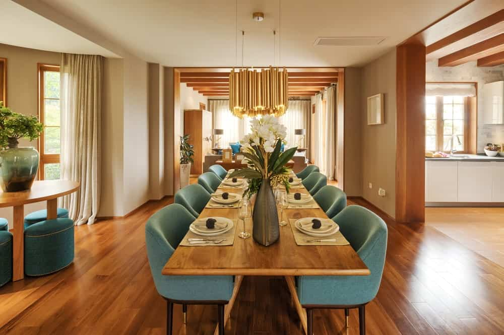 An open dining room with a stylish cluster chandelier and modern blue chairs surrounding a rectangular dining table that blends in with the rich hardwood flooring. It is accompanied by a round wooden table and stools by the bay window.